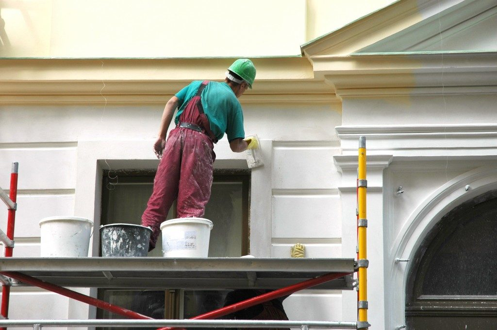 construction worker painting the house wall
