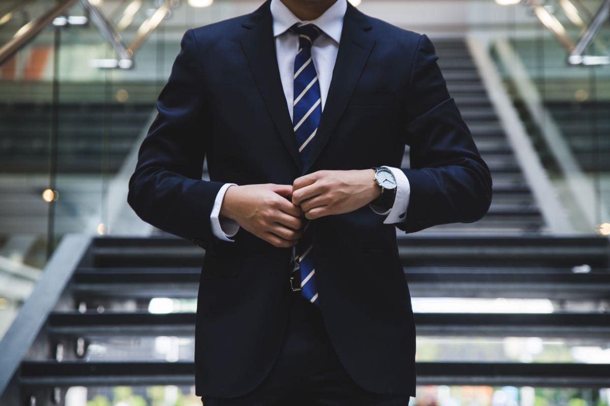 businessman adjusting his suit jacket