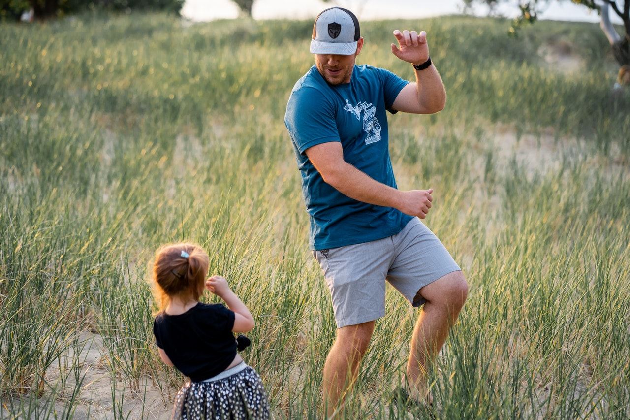 father and daughter dancing outdoors