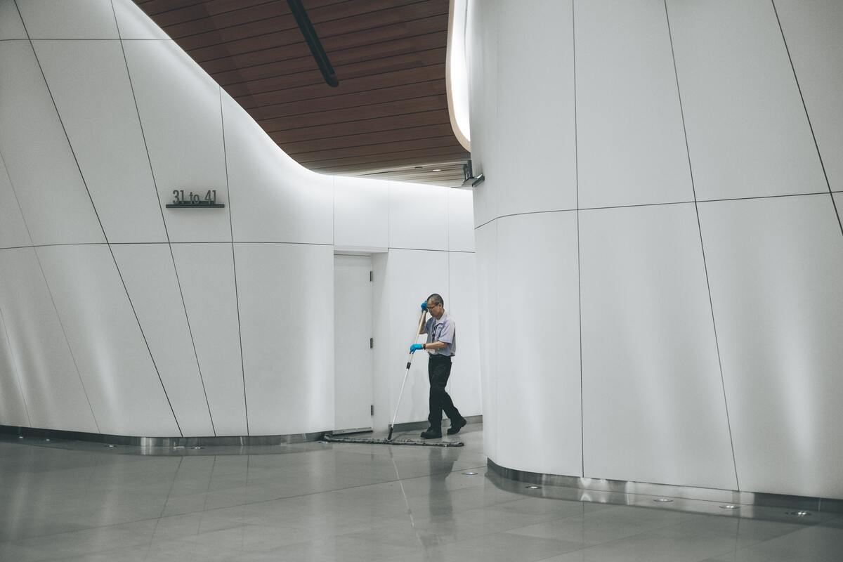 janitor cleaning hallways of office